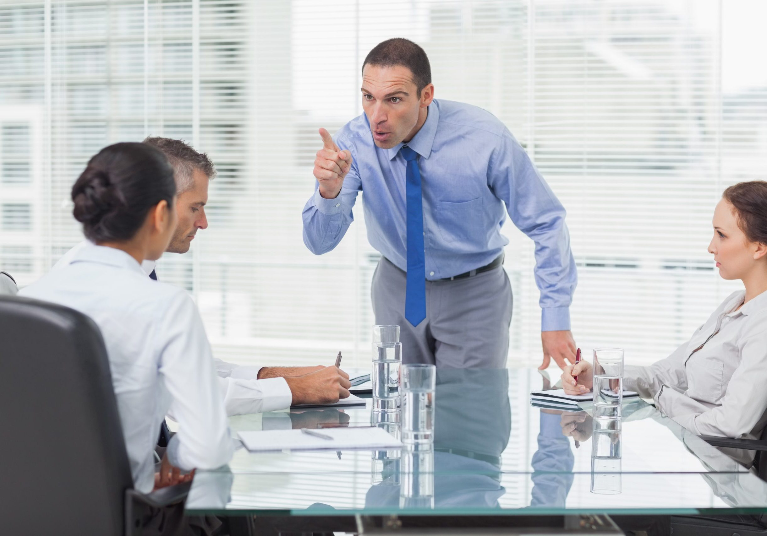 Angry executive pointing out his employee in bright office